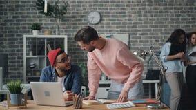 Manliga kollegor som talar diskutera projekt på att göra för bärbar datorskärm som är högt-fem lager videofilmer