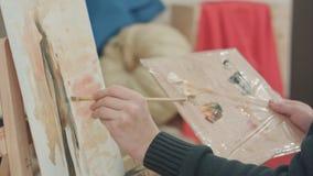 Manliga konstnärhänder som applicerar borsteslaglängder på kanfas och den hållande paletten royaltyfri bild