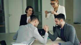 Manliga kontorsarbetare har gyckel som gör arm-brottning, medan flickor antecknar konkurrens genom att använda smartphonen och arkivfilmer