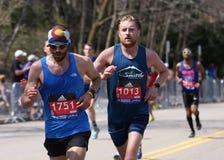 Manliga löpare springer upp hjärtesorgkullen under den Boston maraton April 18, 2016 i Boston Arkivfoton