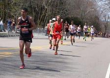 Manliga löpare springer upp hjärtesorgkullen under den Boston maraton April 18, 2016 i Boston Royaltyfri Bild