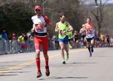 Manliga löpare springer upp hjärtesorgkullen under den Boston maraton April 18, 2016 i Boston Royaltyfria Foton