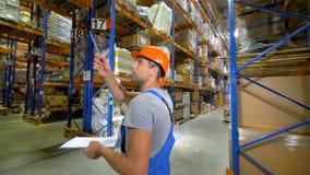 Manliga lageranställda går förbi flera lagergångar stock video