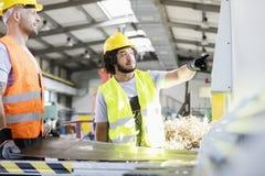 Manliga manuella arbetare som tillverkar arkmetall på fabriken arkivbild