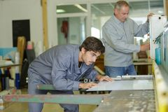Manliga manuella arbetare som undersöker arkmetall på bransch arkivfoton