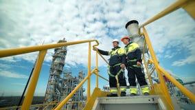 Manliga medarbetare som står på torn och diskuterar industriell säkerhet arkivfilmer