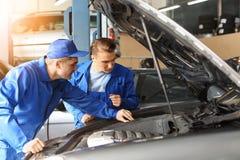 Manliga mekaniker som fixar bilen i servicemitt royaltyfria bilder