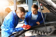 Manliga mekaniker som fixar bilen i servicemitt arkivbild