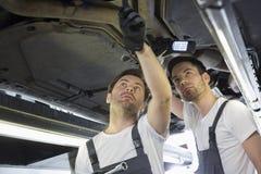 Manliga mekaniker som undersöker bilen i seminarium arkivbild