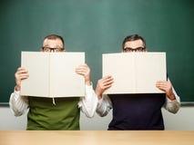 Manliga nerds täckte framsidor med böcker Arkivfoto