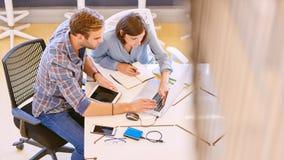 Manliga och kvinnliga affärspartners som tillsammans arbetar på konferenstabellen Arkivbild