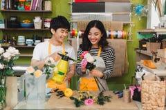 Manliga och kvinnliga blomsterhandlare med härliga buketter i blomsterhandel royaltyfria bilder