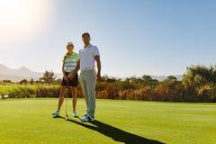 Manliga och kvinnliga golfare på fältet på solig dag Arkivbild