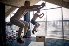 Manliga och kvinnliga idrottsman nen som gör asken, hoppar på idrottshallen Fotografering för Bildbyråer