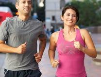 Manliga och kvinnliga löpare på den stads- gatan royaltyfria foton