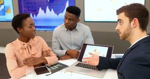 Manliga och kvinnliga ledare som diskuterar över bärbara datorn 4k stock video