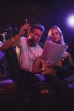 Manliga och kvinnliga musiker som öva med musikark i nattklubb Royaltyfria Bilder