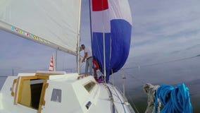 Manliga och kvinnliga sjömän som arbetar på däcket som seglar yachten, fartyg stock video