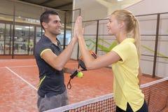 Manliga och kvinnliga tennisspelare som skakar händer över netto Arkivbilder
