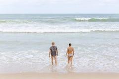 Manliga och kvinnliga turister är avslappnande på stranden i Phuket royaltyfri foto