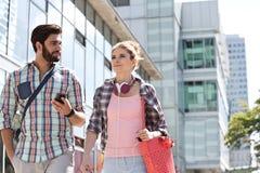Manliga och kvinnliga vänner som går utanför kontorsbyggnad på solig dag Arkivfoto