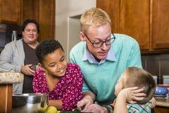 Manliga par och ungar i kök Fotografering för Bildbyråer