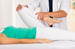 Manliga physio terapeuthänder som arbetar på kvinnliga patientben, innehav och böjer, oskarp klinikbakgrund royaltyfri foto