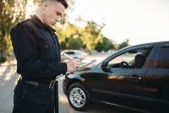Manliga poliser skriver en bot på vägen arkivfoto