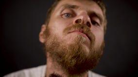 Manliga rakningar för stilig skäggig hipster i det svarta mörka rummet lager videofilmer