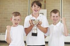 Manliga skolasportar Team In Gym With Trophy Arkivbild