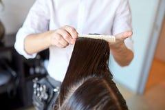 Manliga stylisthänder som kammar vått hår på salongen Arkivbild