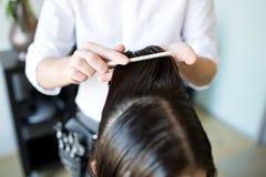 Manliga stylisthänder som kammar vått hår på salongen Arkivfoto