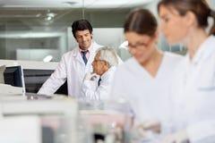Manliga tekniker som diskuterar i labb Royaltyfria Bilder