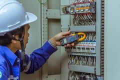 Manliga teknikerer kontrollerar det elektriska systemet med elektroniska hjälpmedel, klämma-på, gemet ampere, klämmameter arkivfoto