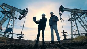 Manliga teknikerer talar, medan stå mellan bränsle som pumpar maskiner Energi olja, gas, bränsle som pumpar riggen stock video
