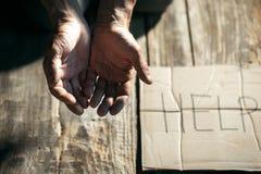 Manliga tiggarehänder som söker pengar på trägolvet på den offentliga banavägen arkivfoton