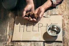 Manliga tiggarehänder som söker pengar på trägolvet på den offentliga banavägen royaltyfri bild