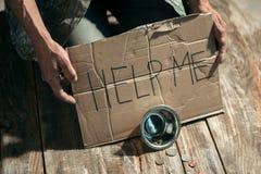 Manliga tiggarehänder som söker pengar på trägolvet på den offentliga banavägen arkivbild