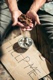 Manliga tiggarehänder som söker pengar på trägolvet på den offentliga banavägen royaltyfria bilder