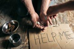 Manliga tiggarehänder som söker pengar på trägolvet på den offentliga banavägen royaltyfri fotografi