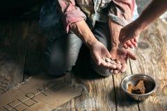 Manliga tiggarehänder som söker pengar på trägolvet på den offentliga banavägen royaltyfri foto