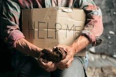 Manliga tiggarehänder som söker pengar på trägolvet på den offentliga banavägen royaltyfria foton
