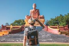 Manliga turister står framme av en stor offentlig skärm i Surin, Thailand royaltyfria bilder