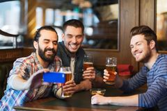 Manliga vänner med smartphonen som dricker öl på stången arkivfoto