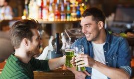 Manliga vänner som dricker grönt öl på stången eller baren arkivbild