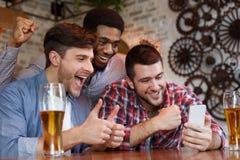 Manliga vänner som har Video-appell på Smartphone i stång royaltyfria foton