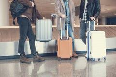Manliga vänner som lokaliserar med baggages i flygplats arkivfoton