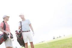 Manliga vänner som samtalar på golfbanan mot klar himmel på solig dag Arkivfoton