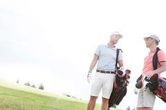 Manliga vänner som samtalar på golfbanan mot klar himmel på solig dag Royaltyfri Bild