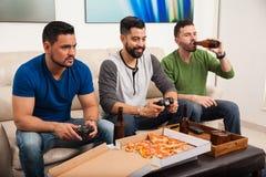 Manliga vänner som spelar videogames fotografering för bildbyråer